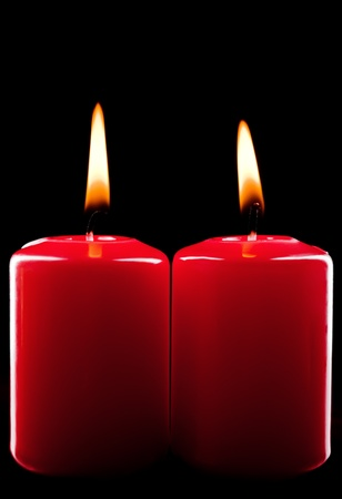 Two red burning candles on black background photo