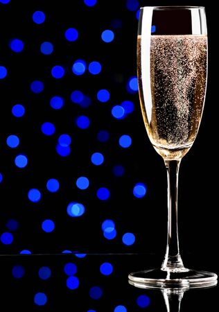 Glass with champagne on abstract color background photo