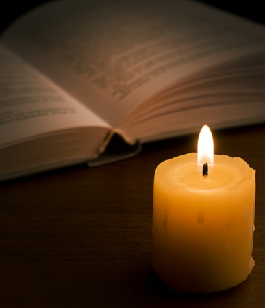 Open book and burning candle on dark photo