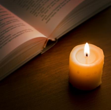 vangelo aperto: Libro aperto e la fiamma di candela sul buio