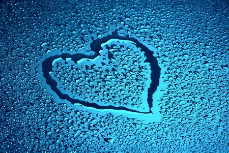 Heart on blue wet surface