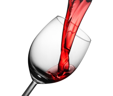 Isolated pouring red wine in the glass Stock Photo