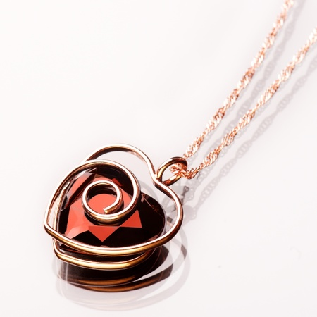 Jewel in the form of heart in a gold frame on a chain