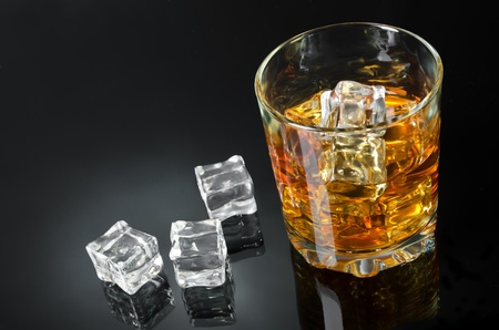 whisky glass: Glass of whisky with ice on a black backdrop Stock Photo