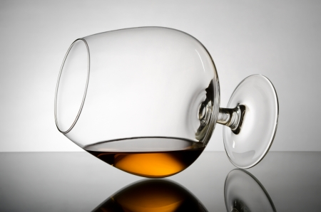 Cognac wineglass lie on glass photo