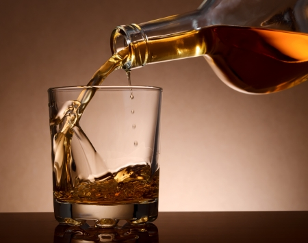 brandy: Pouring malt whisky in a glass from bottle
