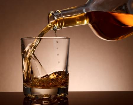botella de licor: Verter el whisky de malta en un vidrio de la botella Foto de archivo