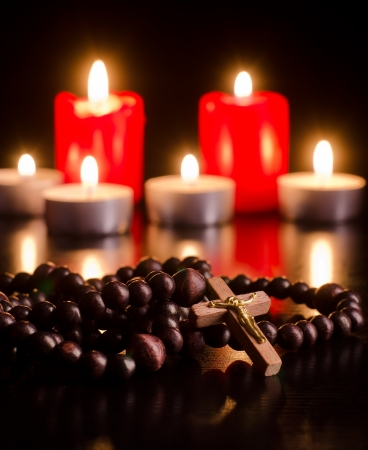 Closeup of wooden rosary on candlelight background photo