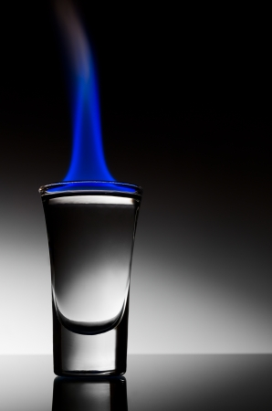 Burning vodka in shot on a black background