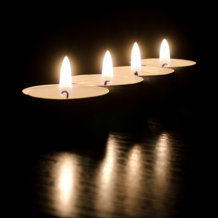Closeup of burning candles on a black background Stock Photo