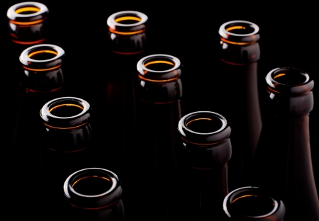 still water: Some open beer bottles on a black background