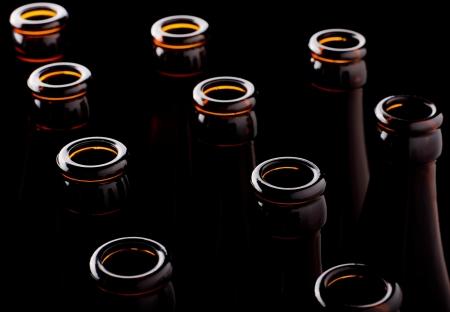 pilsner beer: Some open beer bottles on a black background