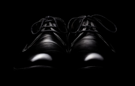 The pair of black leather shoes on a black background photo