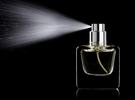 pulverizador: Rociar perfume botella de vidrio sobre un fondo negro aislado Foto de archivo