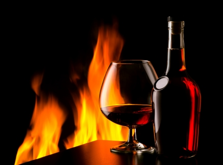 The photo of old cognac on table in front of fireplace photo