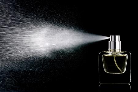分離した黒い背景にガラス瓶香水を噴霧 写真素材