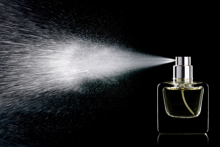 Rociar perfume botella de vidrio sobre un fondo negro aislado