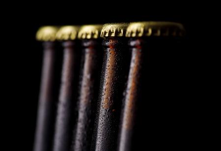 black  cap: Close up bottles of beer on a black background