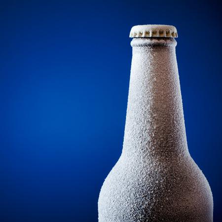 pilsner beer: Frozen glass bottle of beer on blue.