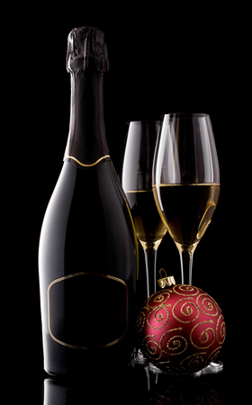Holiday champagne bottle and two champagne glass on a black with christmas tree decoration photo