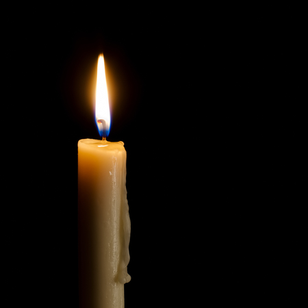 Single burning candle on a black background