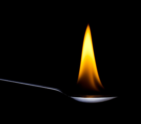 spoons: Fire from spoon on a black background Stock Photo