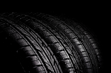 water sports: Car wet tyres on a black background.