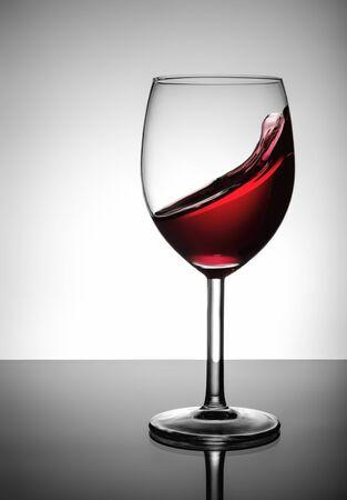 glass of red wine: Splashing red wine in glass Stock Photo