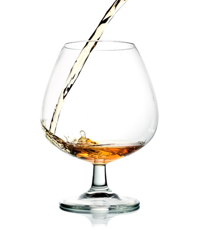 Pouring cognac in wineglass isolated over white