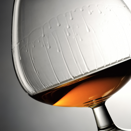 Flowing down drops of cognac in wineglass