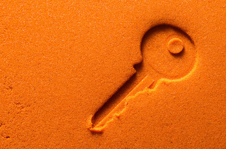 Sign of key on a orange sand texture.