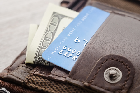 Cash and card money in leather wallet pocket.