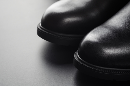 Close up leather boots on a black.