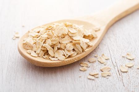 Oat flakes in wooden spoon. Imagens