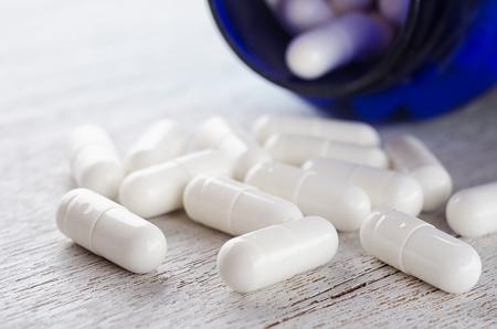 Drug pills from blue bottle.Dietary supplement.