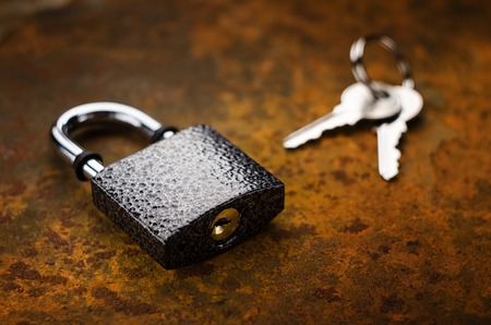 Open padlock with keys on a rusty metal.Secure object. Imagens