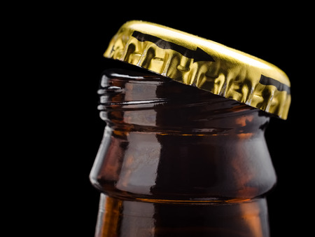 Opened bottle of beer juice cola on a black.