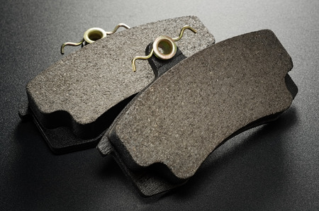 Two automobile brake pads.Black background.