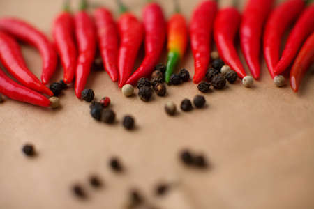 many hot red peppers and peppercorns lying on paper