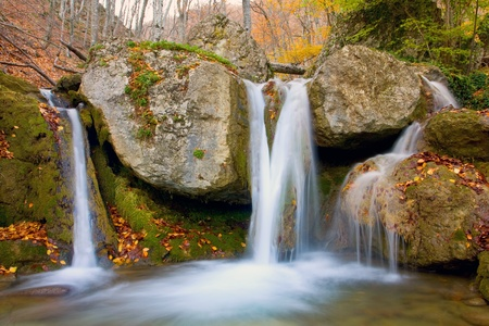 Nice waterfall in autumn forest photo