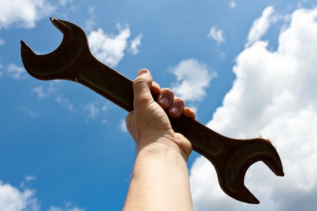 screw key: screw key in man hand on blue sky background