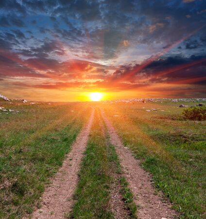 road across steppe to sunset