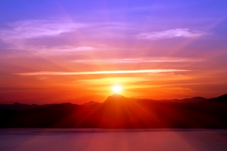 rayos de sol: puesta de sol sobre las montañas cerca del mar