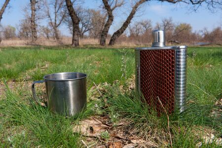Stainless hip flask and cup on grass photo