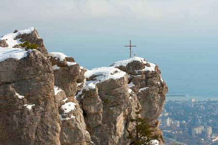 cross on rock in snowy mountain