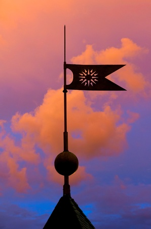 Vane flag on housetop on sunset background photo