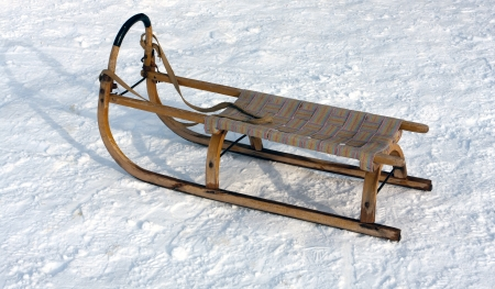 wooden sledge on snow in winter time