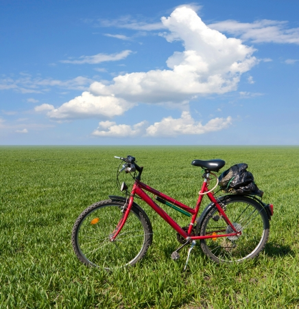 Red bike on green field on nice spring day photo