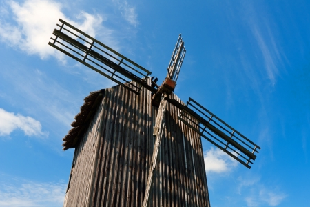 Old wooden windmil on blue sky background photo