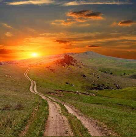 Mountain road on sunset background Stock Photo